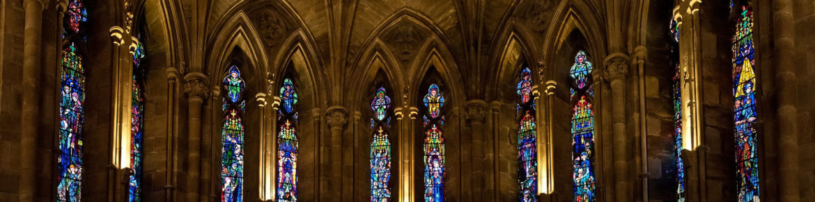 Photo of inside a cathedral with stained glass windows